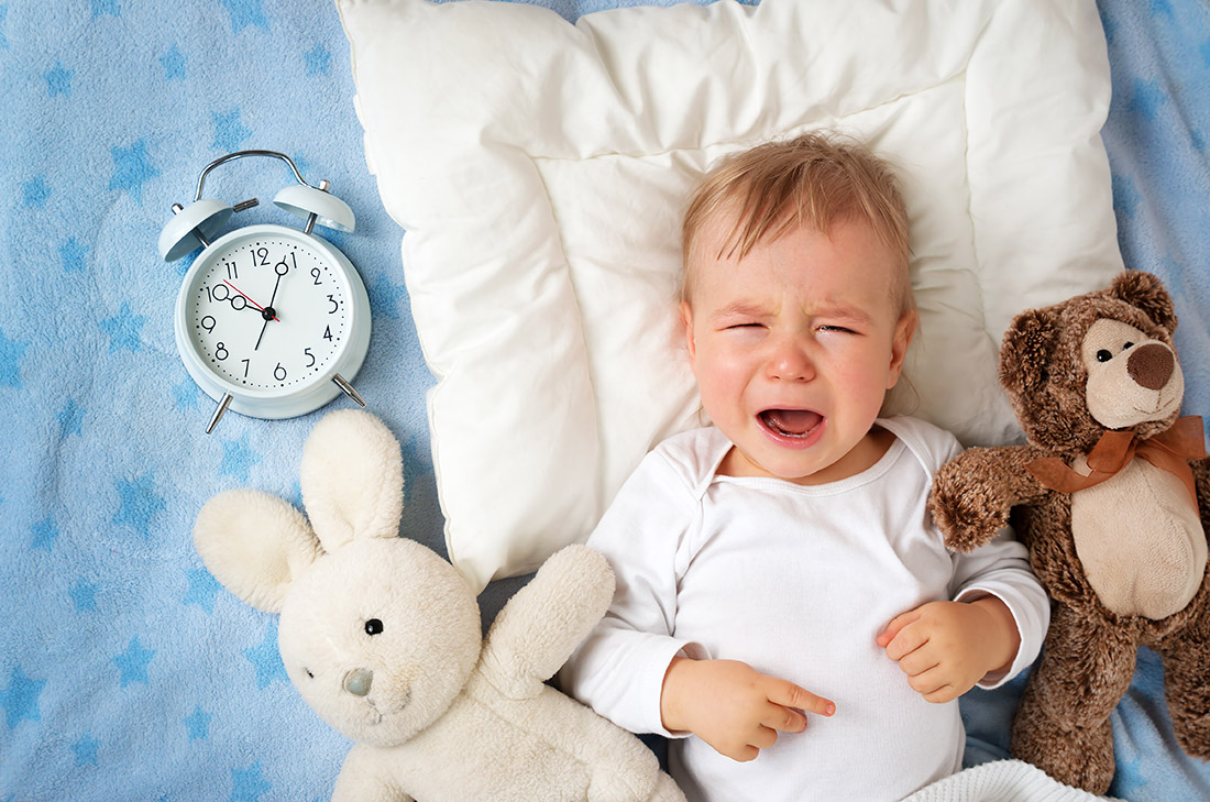 One year old baby lying in bed with alarm clock and crying